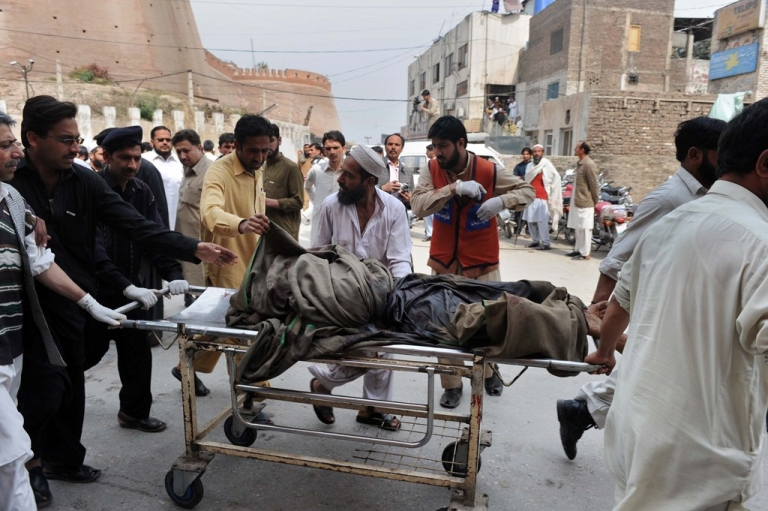 <p>Pakistani relatives and volunteers shift a body from a hospital after a suicide attack in Peshawar on March 11, 2012.</p>