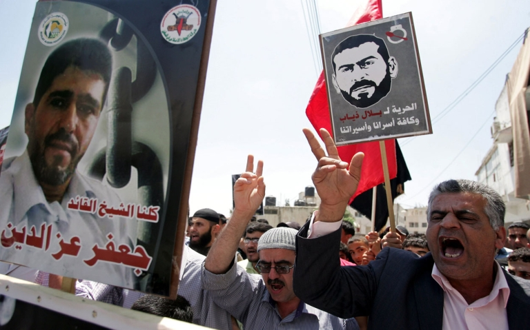 <p>Palestinian protesters shout slogans while holding pictures of prisoners held in Israeli jails during a demonstration in solidarity with jailed hunger strikers in the West Bank village of Kafr Rai near Jenin on May 11, 2012.</p>
