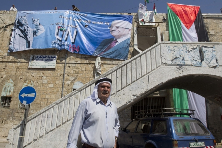 <p>Palestinian municipal employees put in place a huge banner in support of the Palestinian UN bid for statehood at the United Nations on the facade of the former city hall in the northern West Bank city of Tulkarem.</p>