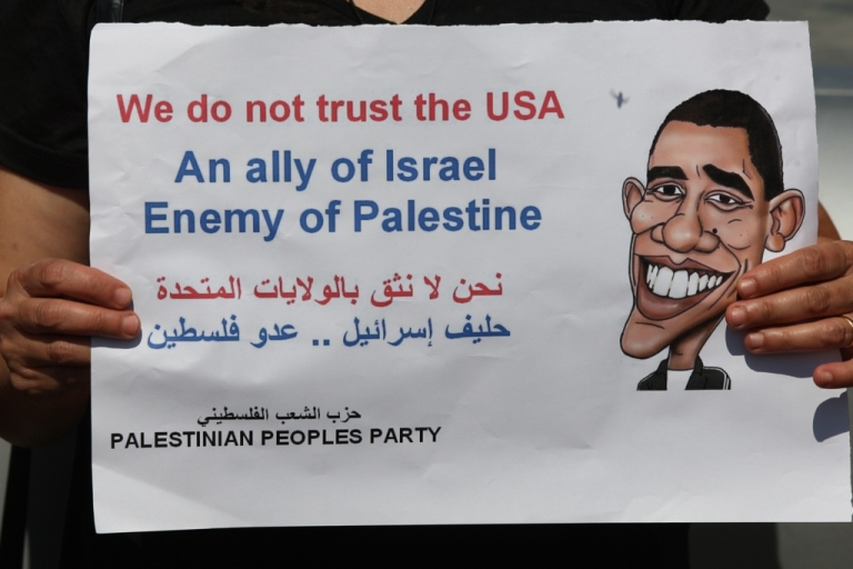 <p>A Palestinian woman holds a sign picturing U.S. President Barack Obama during a protest against U.S. policies towards the Palestinians, ahead a visit by senior US envoys, in the West Bank city of Ramallah on September 7, 2011.</p>
