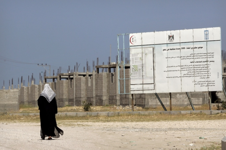 <p>A Palestinian woman walks near an incomplete UN housing project in Rafah, Gaza Strip. Construction in Gaza has ground to a halt due to the Israeli blockade, preventing much needed construction materials from entering and creating widespread poverty and unemployment. Palestine faces economic calamity, according to a new report from a UN agency.</p>
