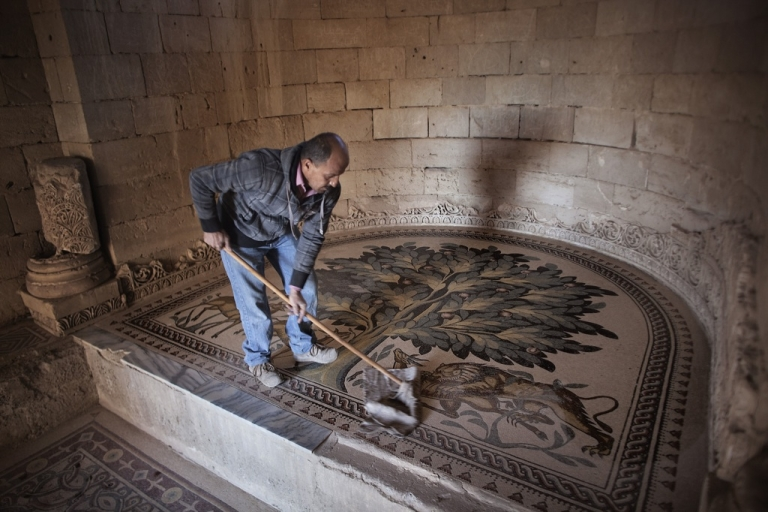 <p>A Palestinian worker cleans the Tree of Life mosaic inside one of the rooms at the ancient Hisham Palace in the West Bank city of Jericho on December 2, 2010.</p>