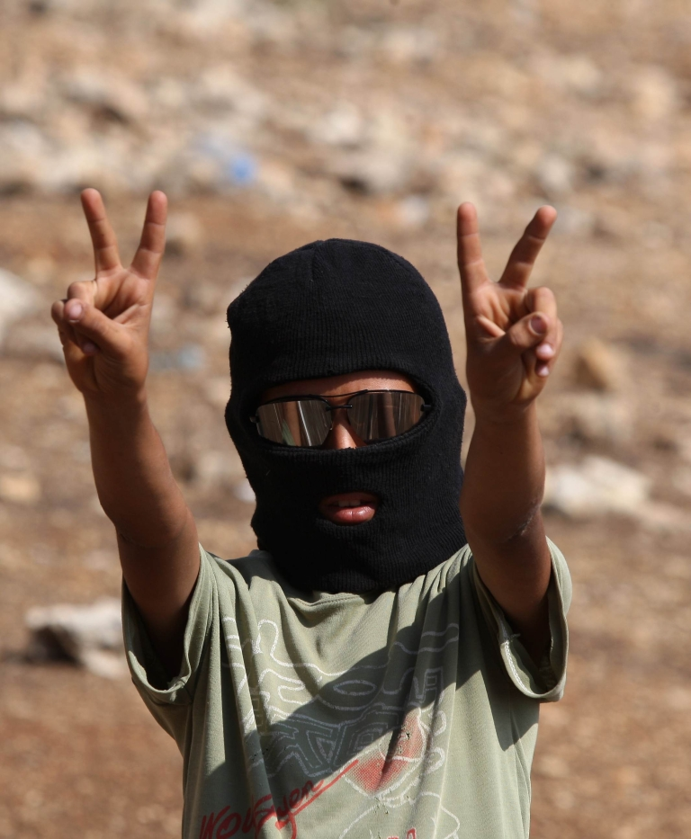 <p>A masked Palestinian youth flashes the 'V' for victory sign during clashes with Israeli forces following a weekly demonstration against Israeli settlement expansion, in the West Bank village of Nabi Saleh, on October 7, 2011. ABBAS MOMANI/AFP/Getty Images</p>