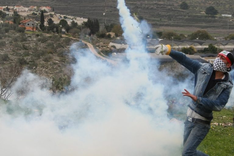 <p>A Palestinian protester throws a tear gas canister back at Israeli soldiers during a demonstration against the expropriation of Palestinian land by Israel in the village of Kfar Kadum near the West Bank city of Nablus on January 13, 2012.    AFP PHOTO/JAAFAR ASHTIYEH</p>