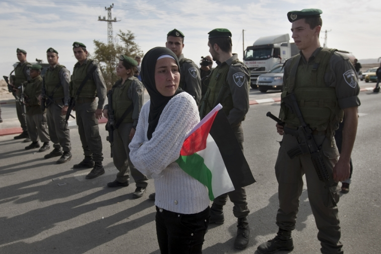 <p>A Palestinian woman holds a national flag as she stands in front of a line of Israeli soldiers blocking the main road leading to the West Bank city of Jericho on January 10, 2012 as some 60 Palestinians tried to drive in a motorcade on Route 60, the main Jewish settler road in the West Bank, to protest against Israeli curbs on Palestinian movement in the West Bank.     AFP PHOTO/AHMAD GHARABLI</p>