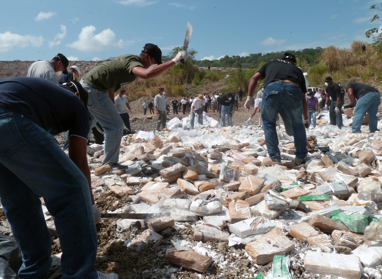 <p>Panamanian policemen smash drug packages with machetes before being incinerated in Cerro Patacon, a dump in Panama City, on Jan.18, 2012. Panamanian authorities burnt 4.9 tons of drugs — 4.4 tons of cocaine, 0.4 tons of marihuana and 0.1 of other drugs.</p>