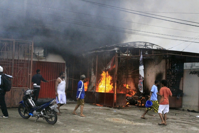 <p>Residents try to extinguish a burning residence torched during riots in the town of Waena in Indonesia's Papua province, Waena on June 14, 2012.  There was also unrest in the provincial capital Jayapura.</p>