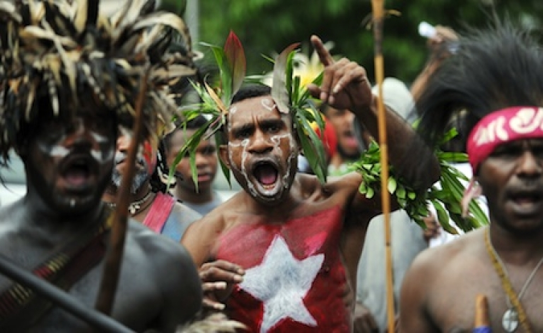 <p>Papuan protesters, their bodies and faces painted in the banned Morning Star flag, shout at a rally marking the 50th anniversary of the region's claim to independence in eastern Indonesia.</p>