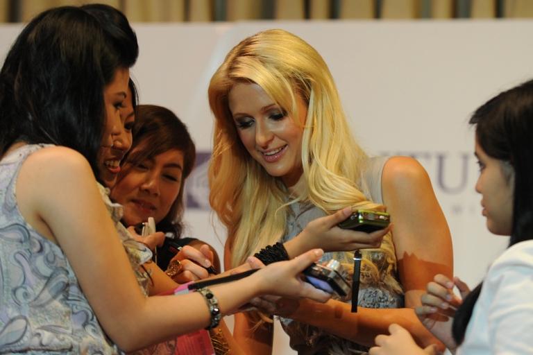 <p>Celebrity socialite Paris Hilton signs autographs in the financial district of Manila on Aug. 17, 2011.</p>