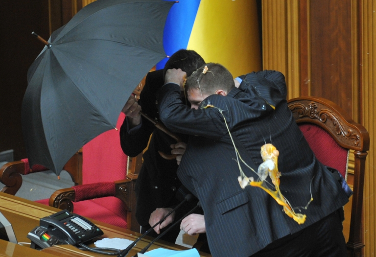 <p>Food often surfaces in political debate in Ukraine. Here, security personnel protect with umbrellas Speaker of Ukraine's parliament Volodymyr Lytvyn during a fight at a parliament sitting in Kiev on April 27, 2010. Smoke bombs and eggs were thrown as Ukraine's parliament ratified a bitterly controversial deal with Russia extending the lease of a key naval base.</p>