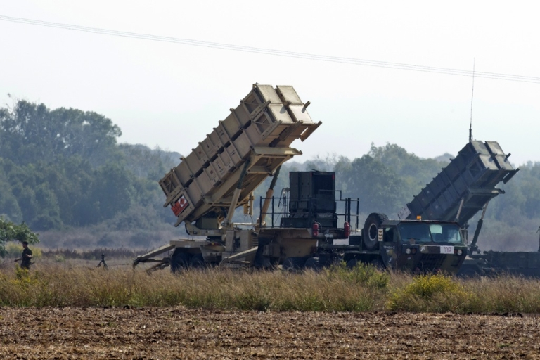<p>An Israli soldier walks nearby two patriot missile batteries, deployed on a field close to Atlit, on the outskirts of Haifa, on Oct. 22, 2012.</p>