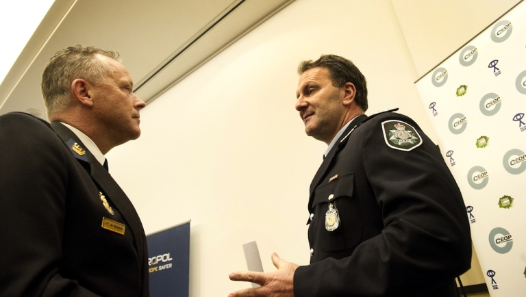 <p>Dutch Joop Scheffer (L) of the Zaanstreek-Waterland police department talks with Australian colleague Grant Edwards on March 16, 2011, before a press conference in The Hague. Europol announced on March 16 that police in several countries had arrested 184 alleged members of an online pedophile ring and rescued 230 children.</p>