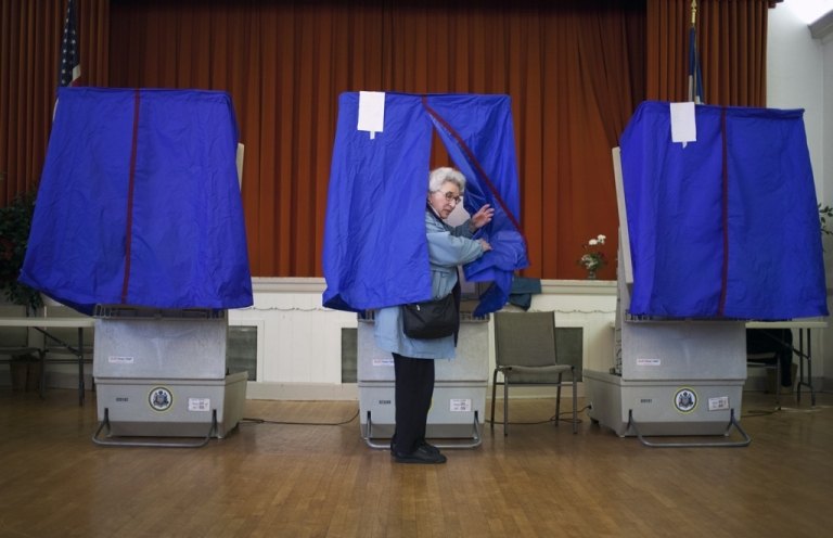 <p>A voter in Pennsylvania takes part in the state's GOP primary election, on April 24, at St. George Greek Orthodox Church in Philadelphia where turnout is expected to be low. Mitt Romney continues his campaign as the presumptive GOP candidate in New Hampshire today.</p>