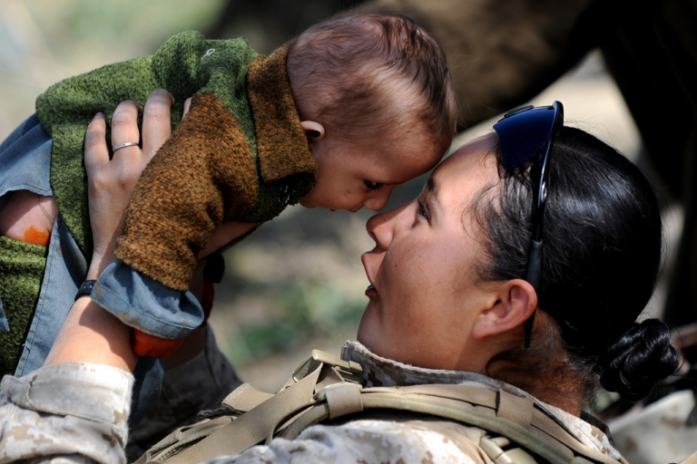 <p>US Marine Lance Corporal Shawnee Redbear of 2nd Battalion, 1st Marines Golf Company interacts with an Afghan toddler during a patrol in Basabad, Helmand Province, on March 9, 2011. The Pentagon changed its policy regarding female soldiers, opening 14,000 combat-related jobs to women as of May 14, 2012.</p>