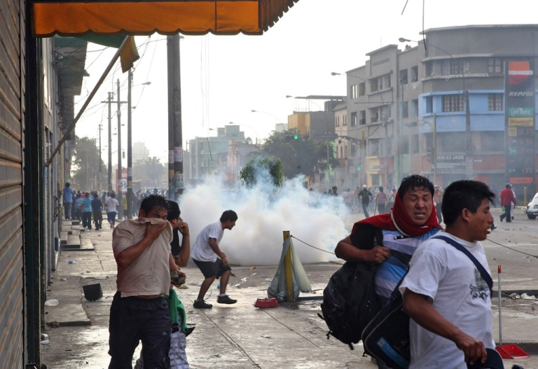 <p>Riot police fire tear gas at protesters during riots at a La Parada market in Lima, on October 25, 2012. Two people were killed and 100 more wounded when clashes erupted Thursday as thousands of police moved in to relocate a crowded wholesale food market in Lima, officials said. The fighting began when the Lima municipality placed concrete blocks at the entrance to the La Parada market to prevent trucks from entering, leading traders to hurl stones in protest and police to respond with tear gas.</p>