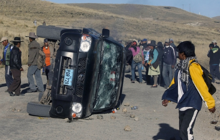 <p>Locals surround a damaged car during a protest against Swiss-owned mining company Xstrata, in the Cuzco province of Espinar, 1,100 km southeast of Lima. At least two people were killed during clashes after hundreds of demonstrators lugged tree trunks and boulders into roads in the Espinar area of Cuzco to protest what they say is the mining firm's pollution of the Salado and Canipia Rivers.</p>
