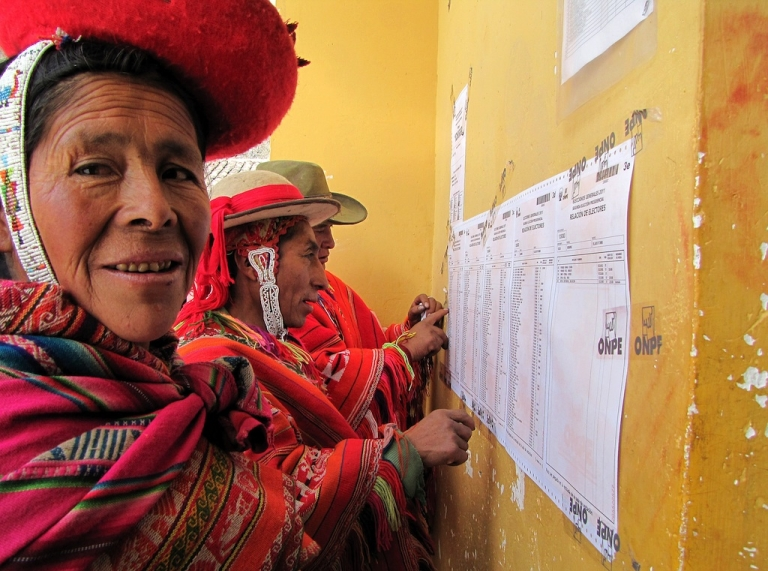 <p>Andean indigenous women wearing traditional clothes look for their registration number at a polling station in the town of Aguas Calientes under the Inca ruins of Machu Picchu, during the presidential elections on June 5, 2011.</p>