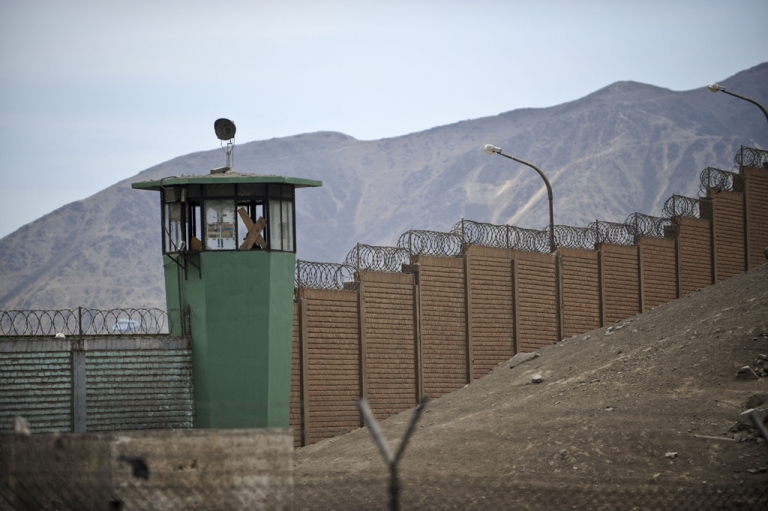 <p>The fence and surveillance tower of the San Juan de Lurigancho prison in Lima, Peru's largest prison.</p>