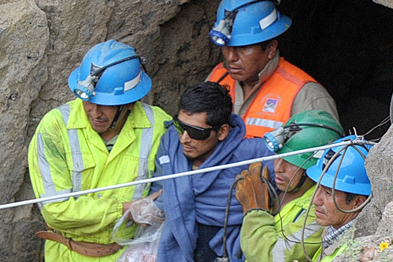 <p>A rescued miner is ushered out of the Cabeza de Negro mine in southern Peru on April 11, after being trapped underground for six days.</p>