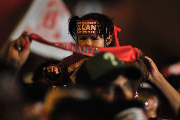 <p>A small girl rides piggy-back during a rally for presidential candidate Ollanta Humala in Lima on April 10, 2011.</p>