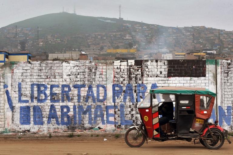 <p>A rickshaw taxi drives past a graffiti reading