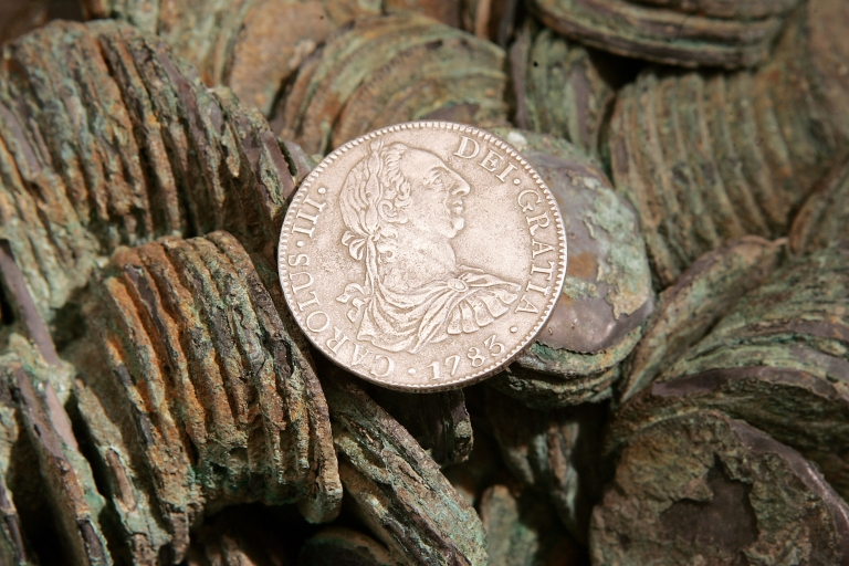 "<p>An 8 Reales Silver coin dated 1783 is seen atop a cluster of those yet to be cleaned from The Franklin Mint's collection recovered from the sunken Spanish ship ""El Cazador.""</p>"