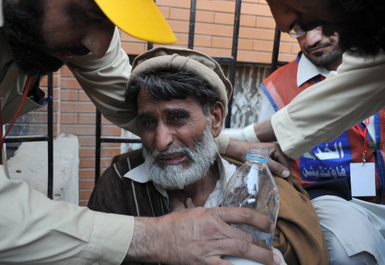 <p>Pakistani volunteers comfort a man whose son was killed in Thursday's car bomb attack in Peshawar.</p>