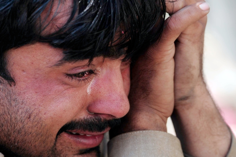 <p>A Pakistani man mourns the death of his brother, one of 12 people killed in Thursday's attack on a bus station near Peshawar.</p>