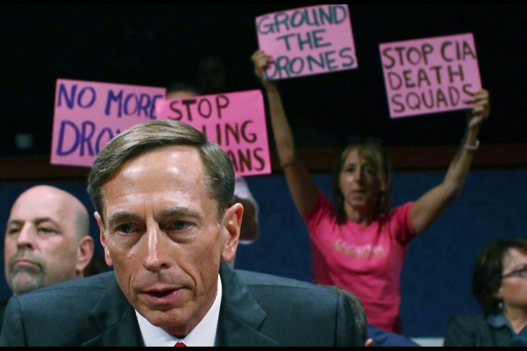 <p>Code Pink protesters stand behind Central Intelligence Agency Director David Petraeus while testifying during a House Select Intelligence Committee and Senate Intelligence Committee joint hearing, on September 13, 2011 in Washington, DC. The</p>
