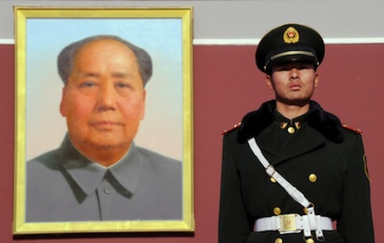 <p>A Chinese paramilitary officer stands beneath a portrait of the late Chinese chairman Mao Zedong as military talks between China and the US open in Beijing on December 7, 2011.</p>