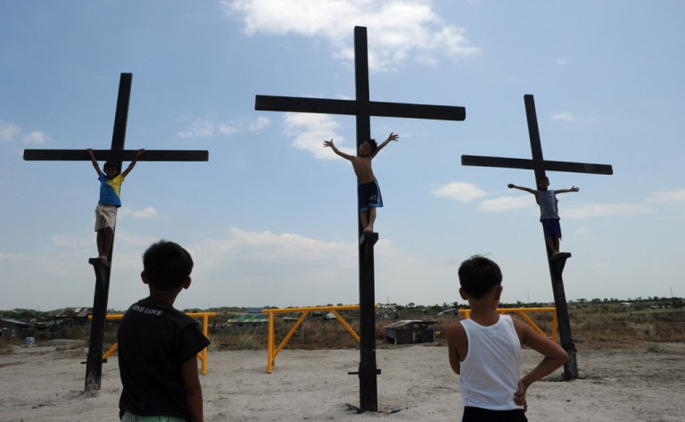<p>Children play on wooden crosses as they mimic the crucifixion in the village of Cutud, in San Fernando, Pampanga province, north of Manila, on April 21, 2011, ahead of the traditional Good Friday Easter celebratations where penintents are nailed to the cross.</p>