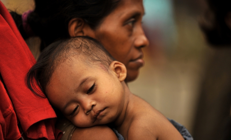 <p>An underpriveleged mother and her child wait in line to receive free bags of Christmas food items from a philanthropist in Manila on December 23, 2010.</p>