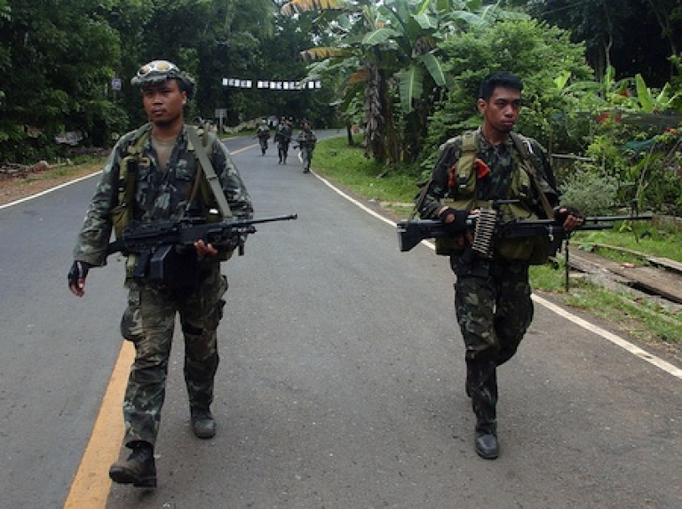 <p>Philippine marines patrol a highway in the southern island of Mindanao on April 14, 2010 as they continue their hunt for militants.</p>