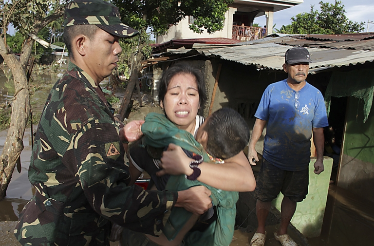 <p>A soldier helps a woman holding the dead body of her child killed during the passage of Tropical Storm Washi at a village in Iligan City, on the Philippines island of Mindanao. More than 650 people were killed, and 800 more are still missing, after the storm triggered widespread flash floods in the southern Philippines.</p>