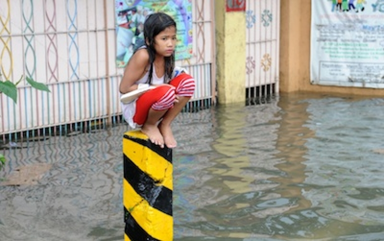 <p>A soaking wet child sits on a post on a flooded street in suburban Manila on August 8, 2012. More than one million people in and around the Philippine capital battled deadly floods on August 8 amid relentless monsoon rains.</p>