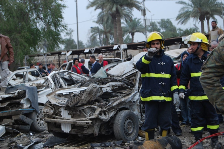<p>Iraqi civil defense workers at the scene of a suicide car bombing outside the appeals court in the Mansour district of Baghdad.</p>