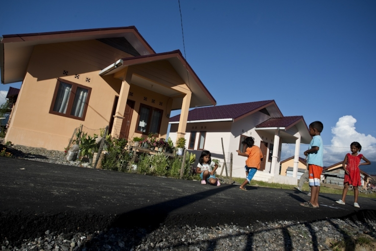 <p>Children play in front of houses built by an aid organization for tsunami victims in Aceh Jaya, Indonesia. The 2004 tsunami destroyed hundred of thousands of houses. Aid groups and government organizations have rebuilt 140,000 houses.</p>