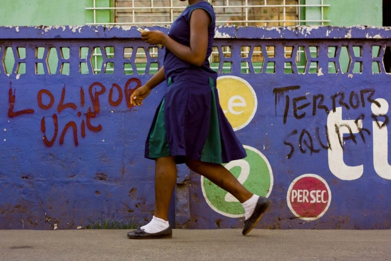 <p>A girl on her way to school in the center of Freetown walks past a house branded in the colors of one of the local cellphone operators. Telecommunications is one of the only growth industries for foreign investment in Sierra Leone. (Tadhg O'Sullivan/GlobalPost)</p>