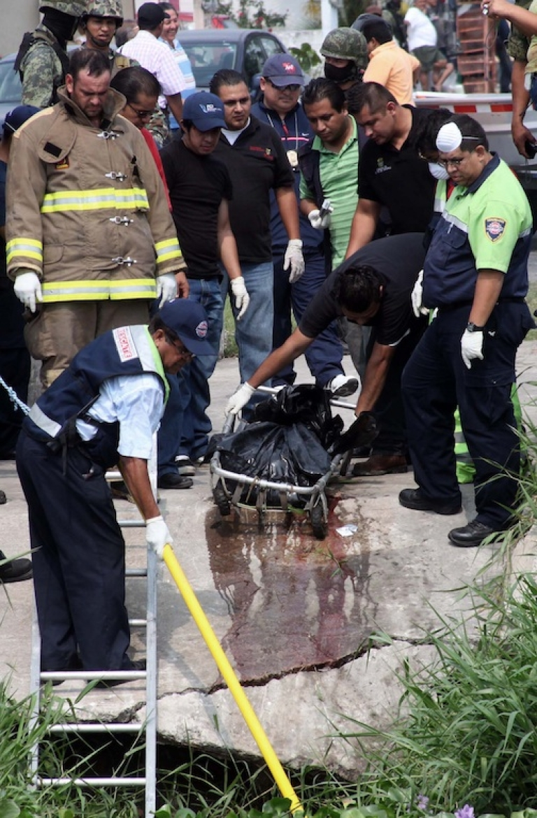 <p>Firefighters and rescuers retrieve plastic bags with the corpses of two news photographers who had disappeared Wednesday afternoon in Veracruz.</p>