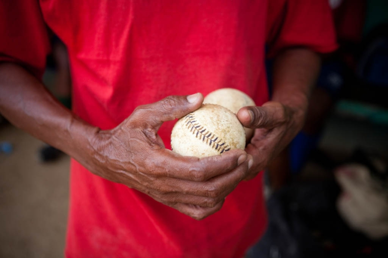 <p>Coach Hector Ramirez holds two baseballs during practice for the Warriors baseball team at the municipal stadium on Thursday, February 25, 2010 in San Antonio de Guerra, Dominican Republic.</p>