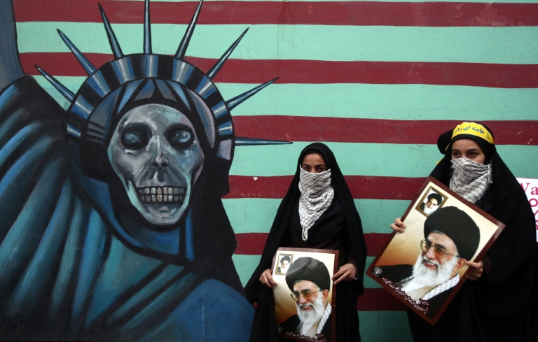 <p>Iranian women hold pictures of Supreme Leader Ayatollah Khamenei outside the former US embassy in Tehran on November 4, 2011, during a rally to mark the storming of the American embassy by Iranian students 32 years ago.</p>