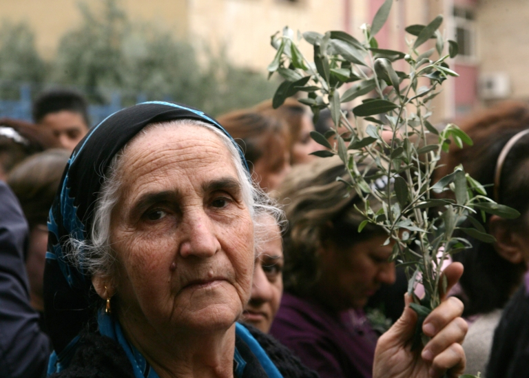 <p>An Iraqi Christian women carries an olive branch in the northern Iraqi Kurdish city of Arbil as Christians gather at the St. Joseph Church, on March 23, 2013, to celebrate Palm Sunday that marks the triumphant return of Jesus Christ to Jerusalem when a cheering crowd greeted him waving palm leaves the week before his death.</p>