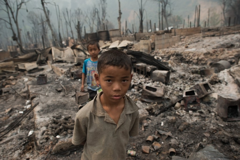 <p>Myanmar refugee boys walk at their destroyed camp at the Mae Surin camp in Mae Hong Son province on March 24, 2013. Thai rescue workers picked through the ashes of hundreds of shelters for Myanmar refugees, after a ferocious blaze swept through a camp in northern Thailand killing 38 people. Around 100 people were injured.</p>