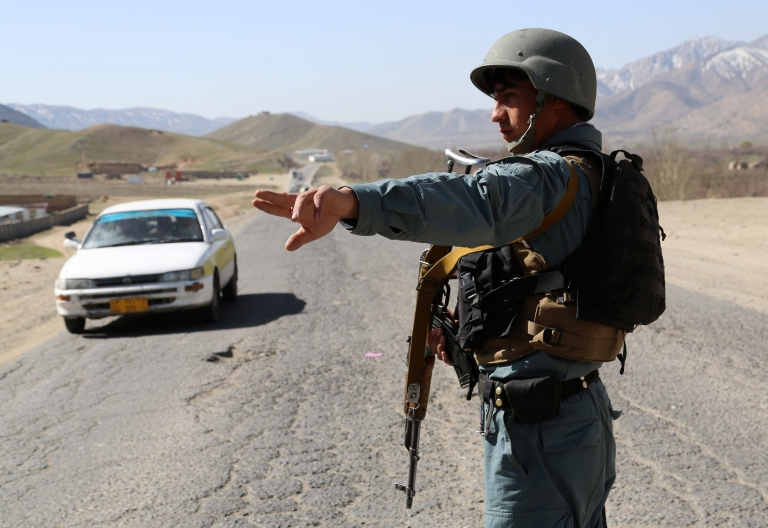 <p>Pierre Borghi, a 29-year-old French freelance photographer, escaped his Taliban captors this week after four months of captivity. Above an Afghan policeman directs a vehicle at a checkpoint in Wardak province on April 4, 2013.</p>