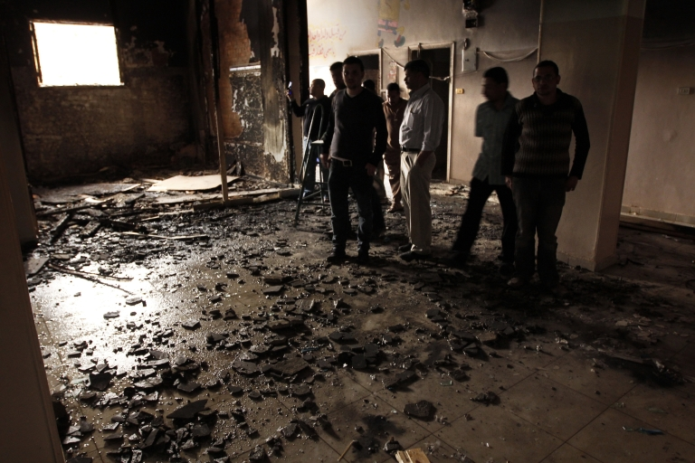 <p>People inspect the inside of a the destroyed room in a building that was burnt down during a night of sectarian clashes between Christians and Muslims in Al-Khusus, a poor area in Qalyubia governorate, north of Cairo on April 6, 2013.</p>