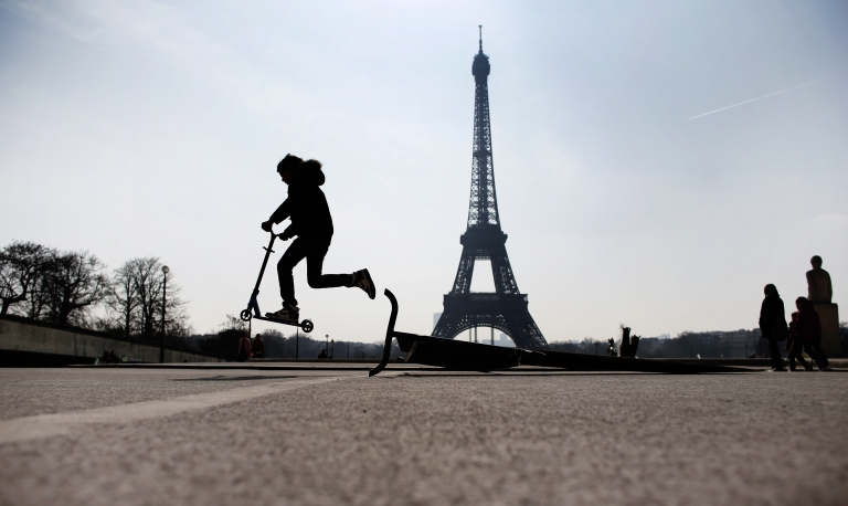 <p>A child rides a scooter on the Trocadero square, in front of the Eiffel tower, on April 7, 2013.</p>