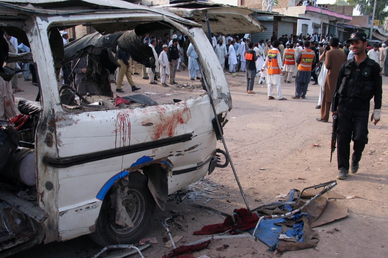 <p>Pakistani security personel and rescuers gather at the site of a bomb blast in Peshawar on April 13, 2013.</p>