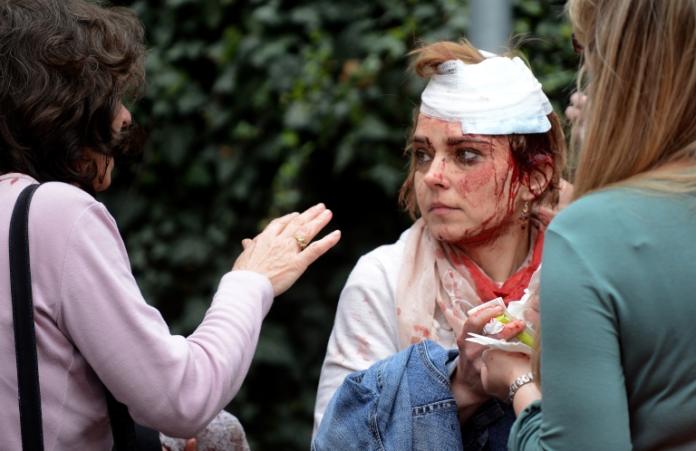 <p>Injured people stand on the street near the site of a powerful gas blast in Prague's historic center on April 29, 2013. The blast injured up to 20 people, four seriously, rescuers said, adding that it was possible some people were buried in the rubble.</p>