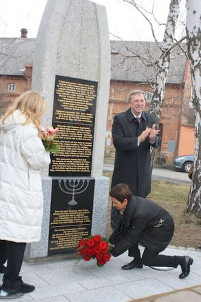 <p>Eva Vavreckova, whose mother Felicitas survived three years of World War II hiding in the woods and other makeshift shelters, with the aid of the villagers of Trsice, lays flowers at the memorial honoring them. Joan E. Silber of the US Commission for the Preservation of America's Heritage Abroad and Czech Senator Martin Tesařík watch.</p>
