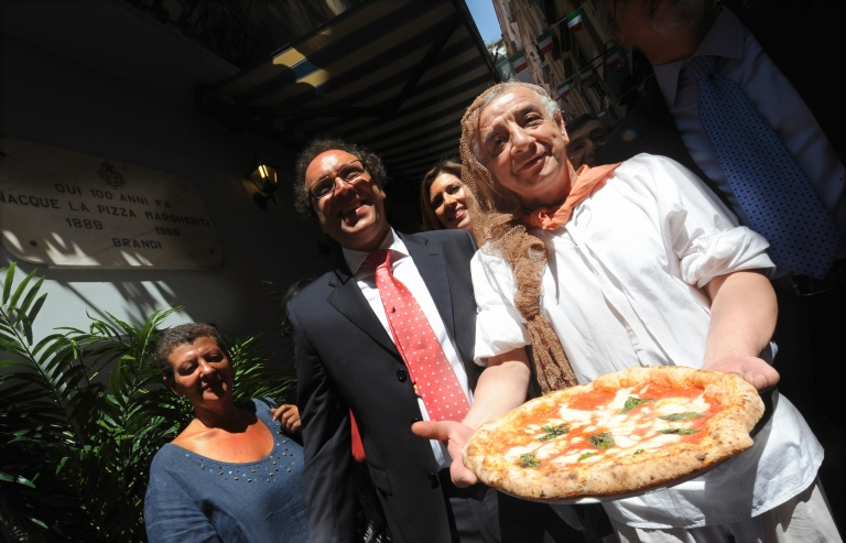 <p>A pizzaiolo of the Brandi restaurant holds a pizza named after Queen Margherita of Savoy during a ceremony to celebrate the 120th anniversary of the pizza Margherita on June 11, 2009 in Naples.</p>